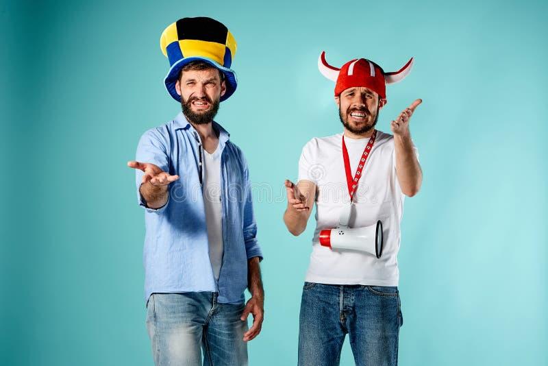 Die zwei Fußballfane mit Mundstück über Blau lizenzfreie stockbilder
