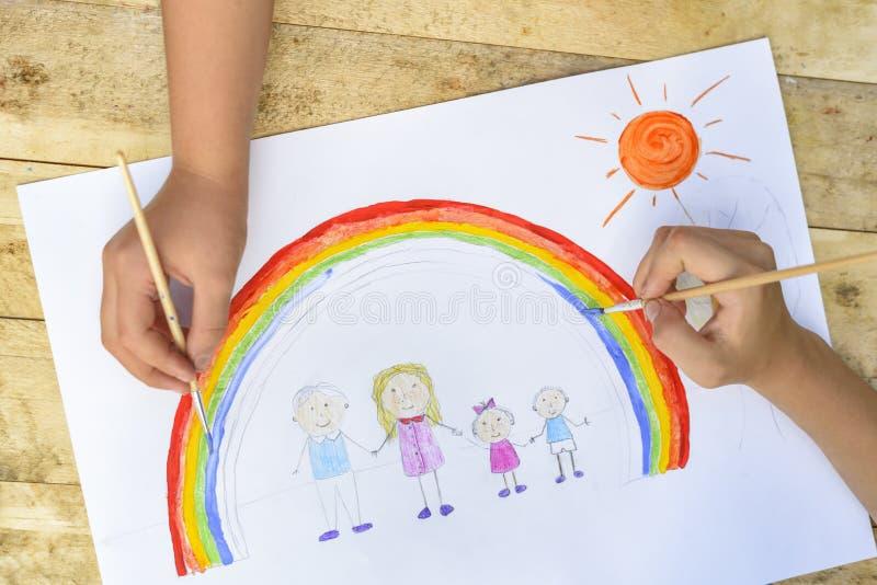 Die zwei Hände der Kinder zeichnen eine Zeichnung mit einer Bürste und Farben oberseite stockfotografie