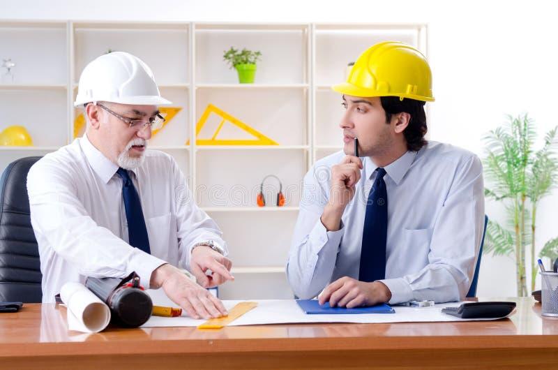 Die zwei Ingenieurkollegen, die unter Projekt arbeiten lizenzfreie stockbilder