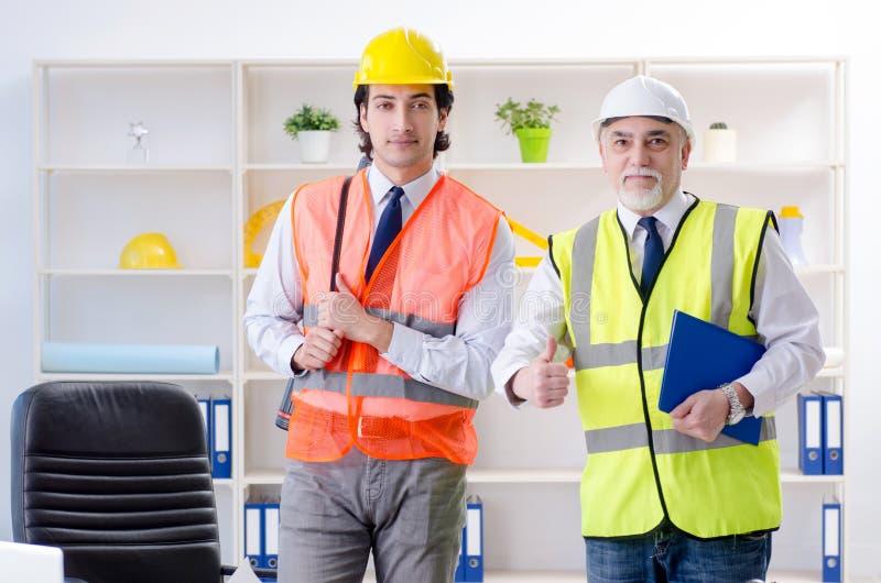 Die zwei Ingenieurkollegen, die unter Projekt arbeiten stockfotografie