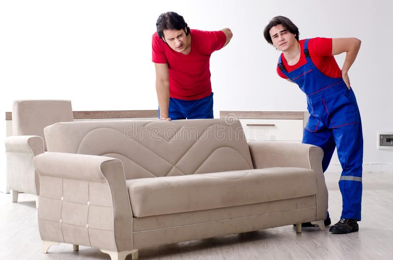 Die zwei jungen Auftragnehmerangestellten, die pers?nliches Eigentum bewegen stockbilder