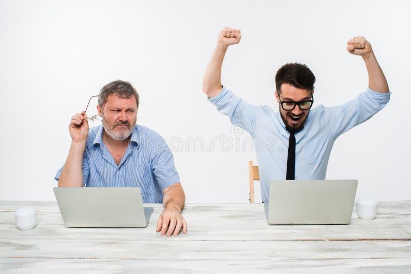 Die zwei Kollegen, die im Büro auf weißem Hintergrund zusammenarbeiten stockbilder