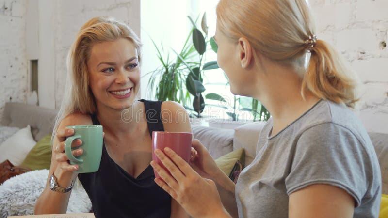 Die zwei Mädchen trinken Kaffee stockfotos
