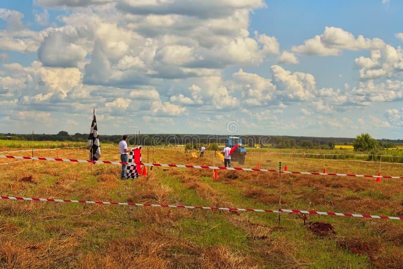 Die zwei Richter passen auf, während der Teilnehmer die Bahn führt Stellen Sie steuernden Wettbewerb am Feld dar Beerenfestival B lizenzfreie stockfotografie