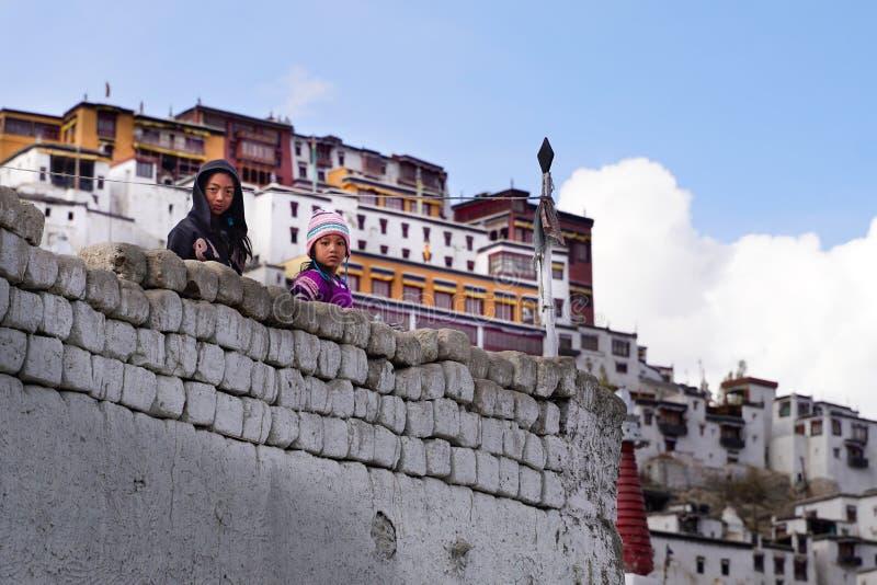 Die zwei tibetanischen Mädchen, die von der Wand bleiben und schauen lizenzfreie stockfotografie