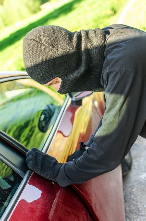 Dieb bricht die Tür im Auto stockbild
