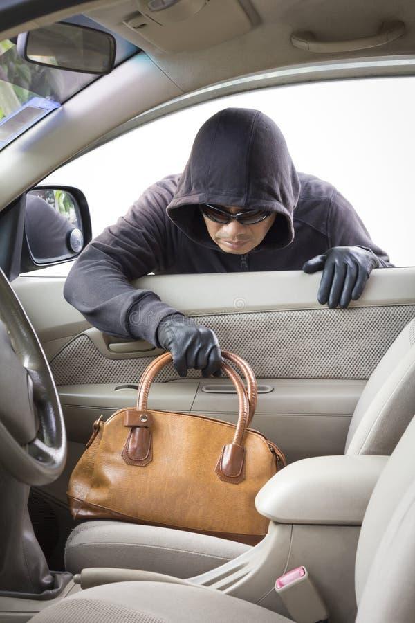 Dieb, der Handtasche vom Auto stiehlt stockbild