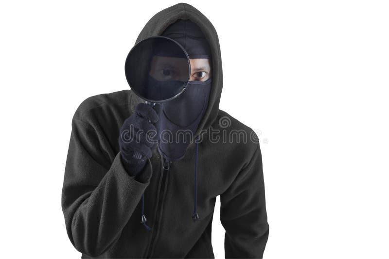 Dieb mit Lupe für die Spionage stockbild