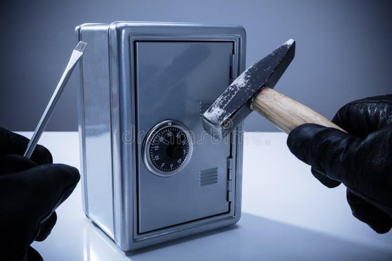 Dieb-Using Screwdriver And-Hammer, zum des Safes zu öffnen lizenzfreies stockfoto