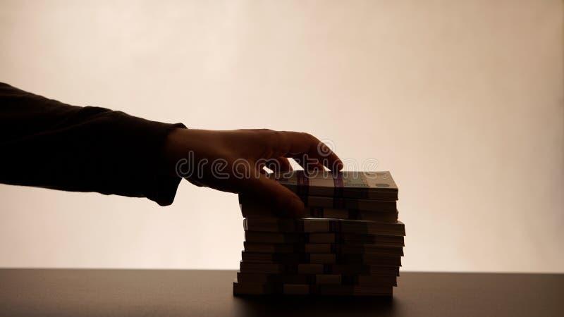 Diebstahl des Geldes vom Stapel lizenzfreie stockfotografie