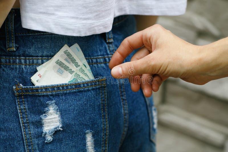 Diebstahl des Geldes von der Rückseite Ihrer Jeanstasche lizenzfreie stockfotografie