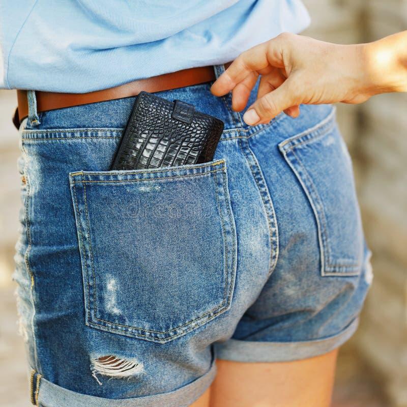 Diebstahl einer Geldbörse von seiner Tasche in der Tageszeit auf der Straße stockbilder