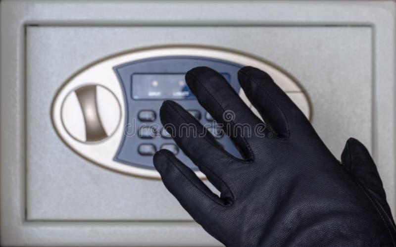 Diebstahl von Wertsachen oder von Geld vom Safe Eine schwarz-behandschuhte Hand drückt die Knöpfe für ein Kombinationsschloß  stockfoto