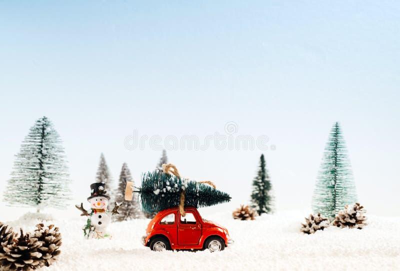 Diecast модельный автомобиль носит рождественскую елку в плаще снежного и зимы стоковое фото
