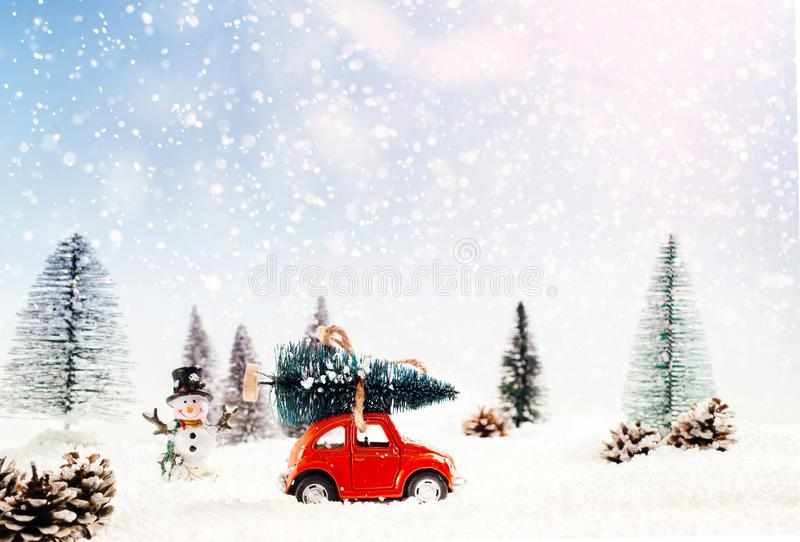 Diecast model car carries the Christmas tree in a snowy and winter cloak royalty free illustration