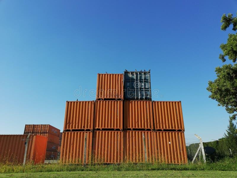 Dieci contenitori accatastati su con un fondo del cielo blu fotografie stock libere da diritti