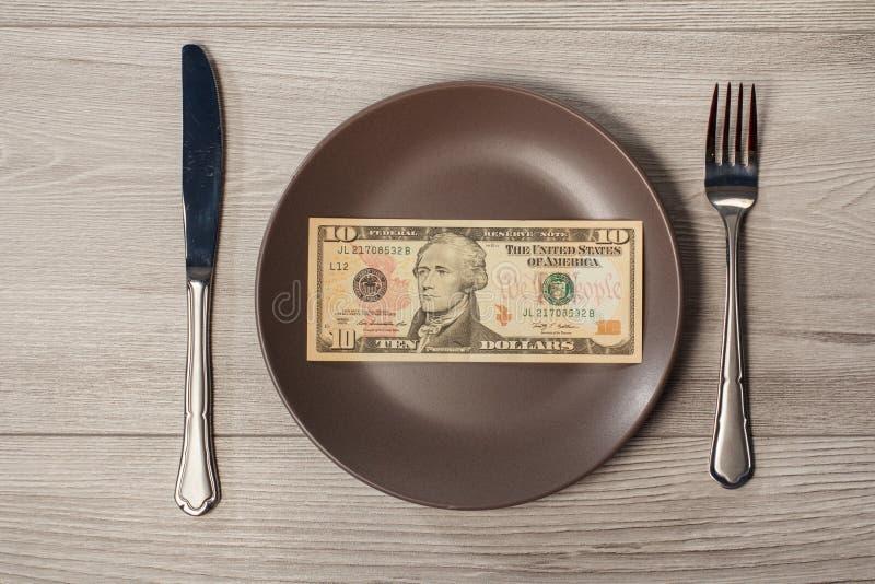 Dieci dollari di fattura americani sul piatto del patè di maiale con la forcella ed il coltello Mo fotografia stock