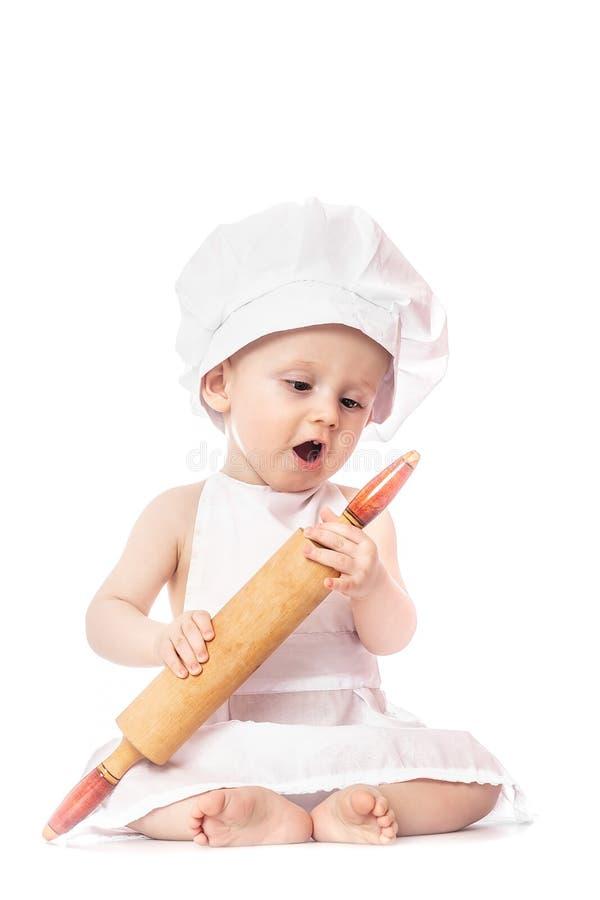 Dieci mesi del bambino in un vestito del cuoco sorpreso e che sorride nella cucina Piccolo bambino come un piccolo cuoco o sculli immagini stock