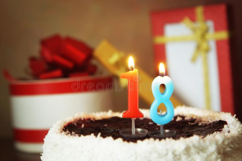 Dieciocho años de cumpleaños Torta con la vela y los regalos ardientes imagen de archivo libre de regalías