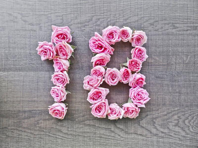 18, dieciocho - número del vintage de rosas rosadas en el fondo de la madera oscura foto de archivo