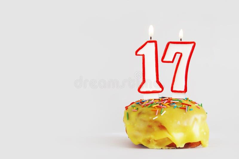 Diecisiete años de aniversario Magdalena del cumpleaños con las velas ardientes blancas con la frontera roja bajo la forma de núm fotos de archivo