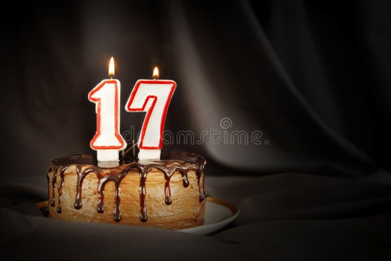 Diecisiete años de aniversario Torta de chocolate del cumpleaños con las velas ardientes blancas bajo la forma de número diecisie fotografía de archivo