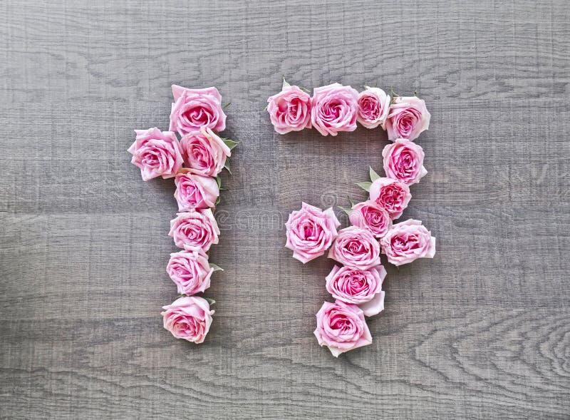 17, diecisiete - número del vintage de rosas rosadas en el fondo de la madera oscura foto de archivo libre de regalías