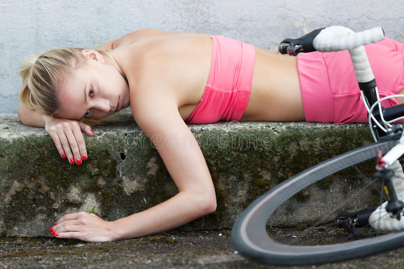 Died for sport. Exhausted girl laying on the ground after bicycle race stock photo