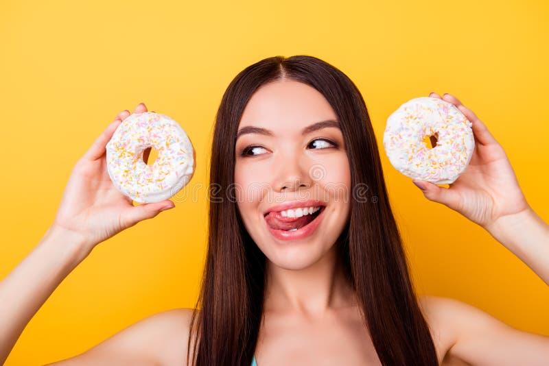 Dieet en calorieënconcept Sluit omhoog portret van het gelukkige Aziatische meisje kijken op donutes met tounge uit, zo speels en royalty-vrije stock afbeeldingen
