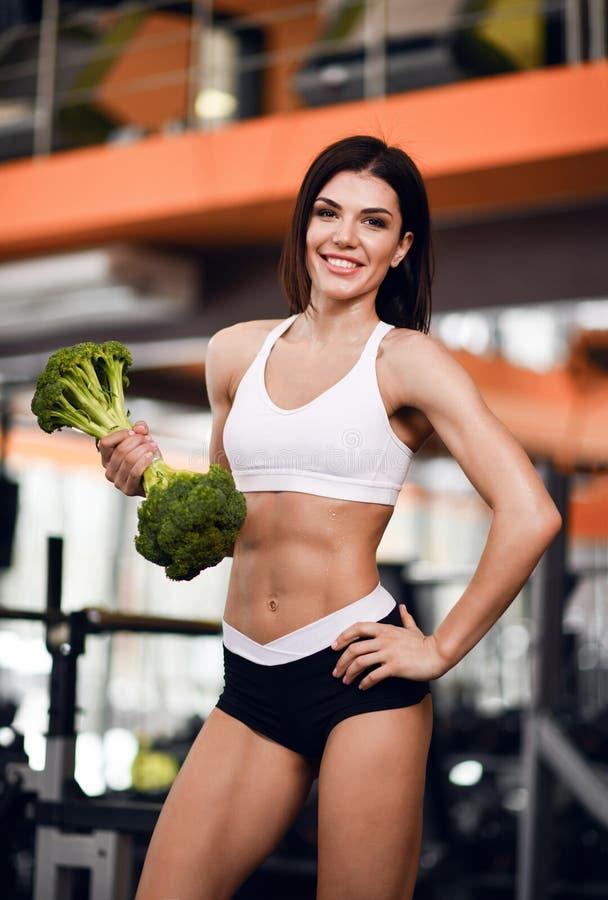 Dieet en Geschiktheidsconcept De gelukkige sportieve instructeur van de meisjesgeschiktheid in sportkleding werkt bicepsen met gr royalty-vrije stock fotografie