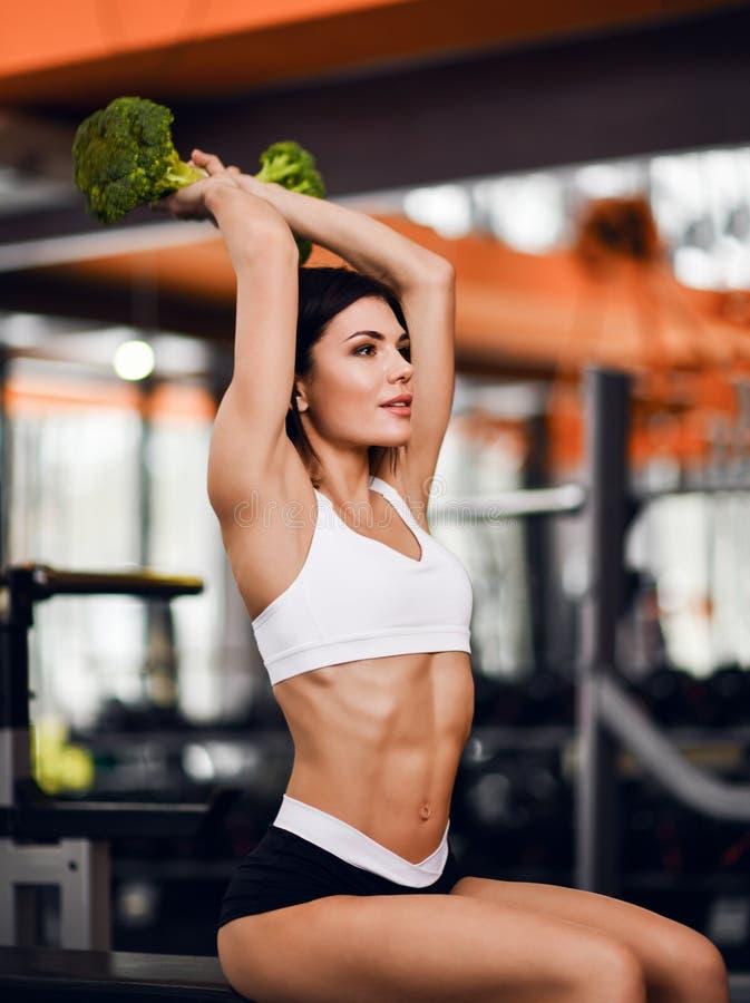 Dieet en Geschiktheidsconcept De jonge atletische instructeur van de meisjesgeschiktheid leidt haar triceps met grote groene broc royalty-vrije stock foto's