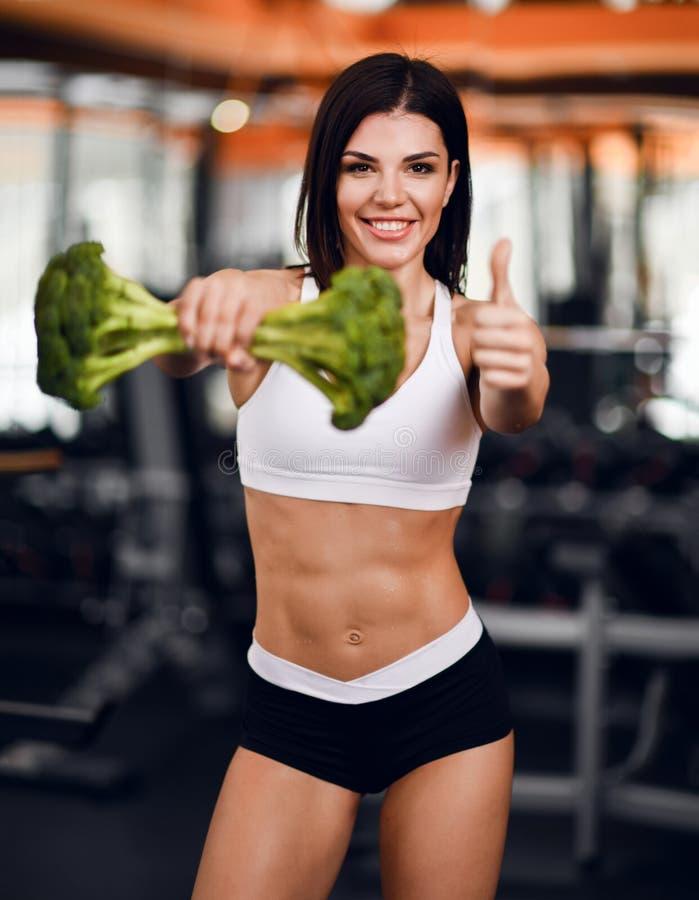 Dieet en gewichtsverliesconcept De gelukkige glimlachende atletische instructeur van de meisjesgeschiktheid overhandigde ons grot royalty-vrije stock afbeelding