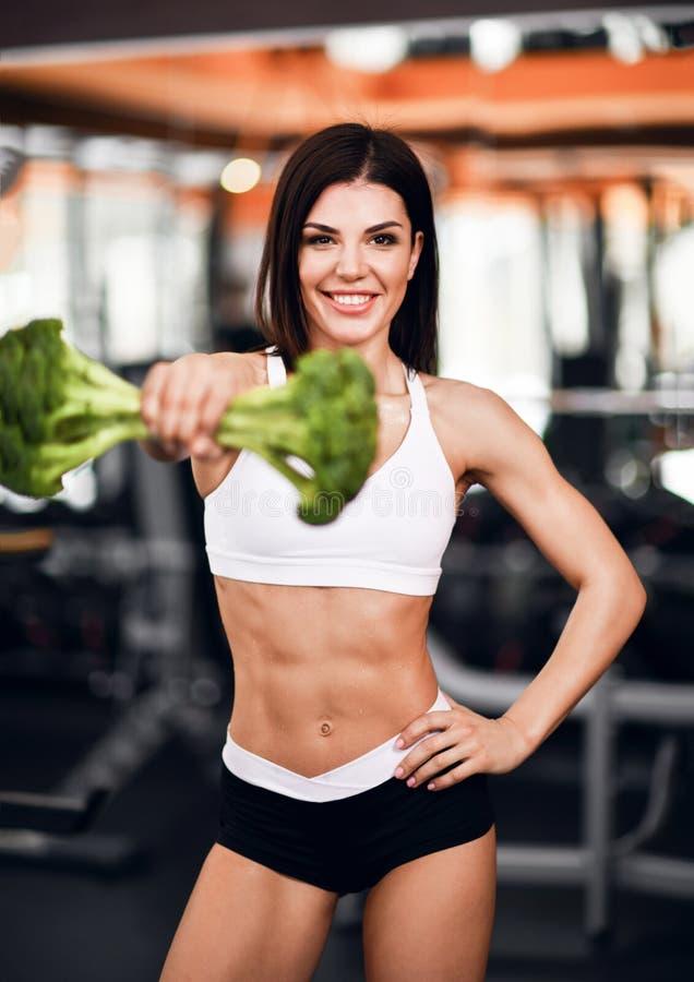 Dieet en gewichtsverliesconcept De speel atletische instructeur van de meisjesgeschiktheid in sportkledingsstempels met broccoli  stock fotografie