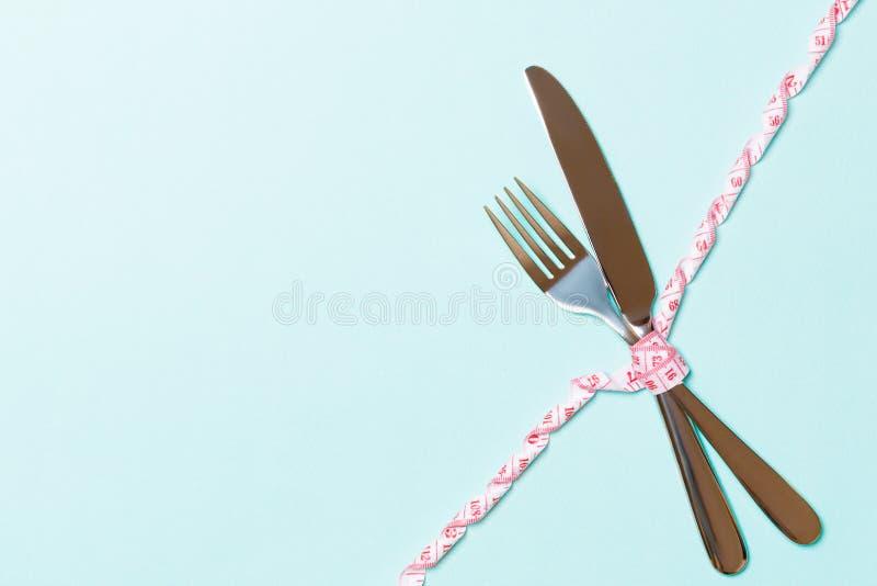 Dieet en gezond het eten concept met gekruist vork en mes en gekruld metend band op blauwe achtergrond Hoogste mening van weightl royalty-vrije stock fotografie
