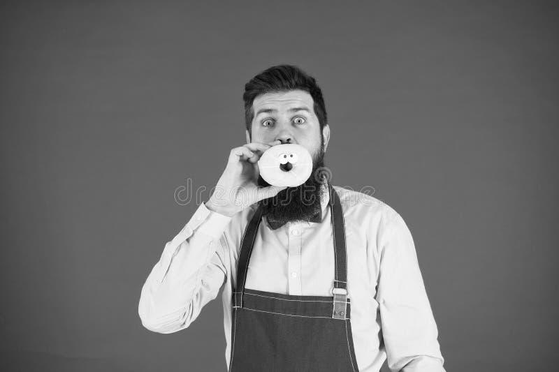Dieet en gezond voedsel Baker eet doughnut Chef-kokmens in koffie calorie Voel honger Gebaarde bakker Gebaarde Mens in Schort royalty-vrije stock afbeeldingen