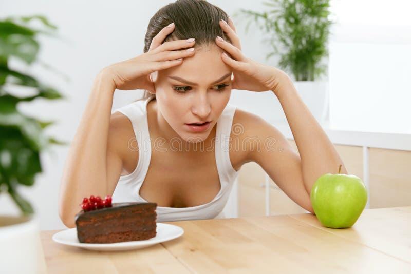 Dieet en voeding Vrouw die tussen Cake en Apple kiezen royalty-vrije stock foto