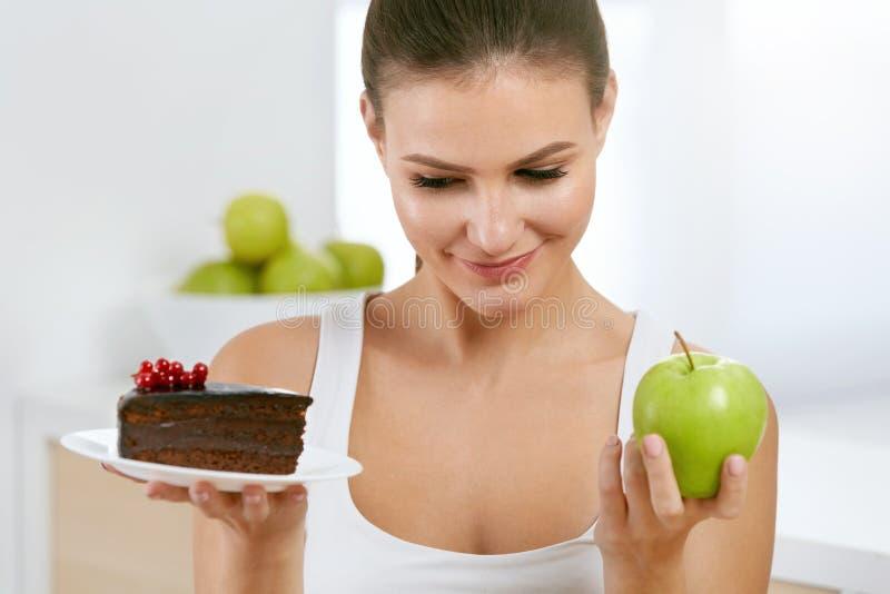 Dieet en voeding Vrouw die tussen Cake en Apple kiezen stock afbeelding