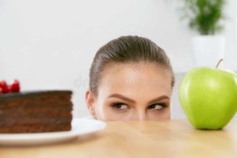 Dieet en voeding Vrouw die tussen Cake en Apple kiezen stock afbeeldingen