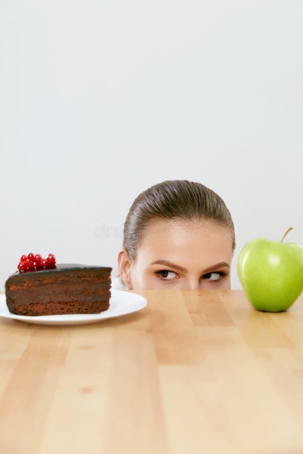 Dieet en voeding Vrouw die tussen Cake en Apple kiezen stock foto