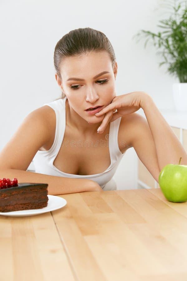 Dieet en voeding Vrouw die tussen Cake en Apple kiezen royalty-vrije stock foto's