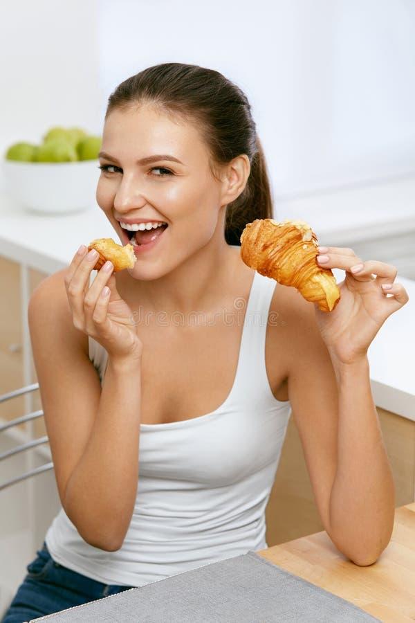 Dieet Gelukkige Vrouw die Croissant voor Ontbijt eten stock afbeelding