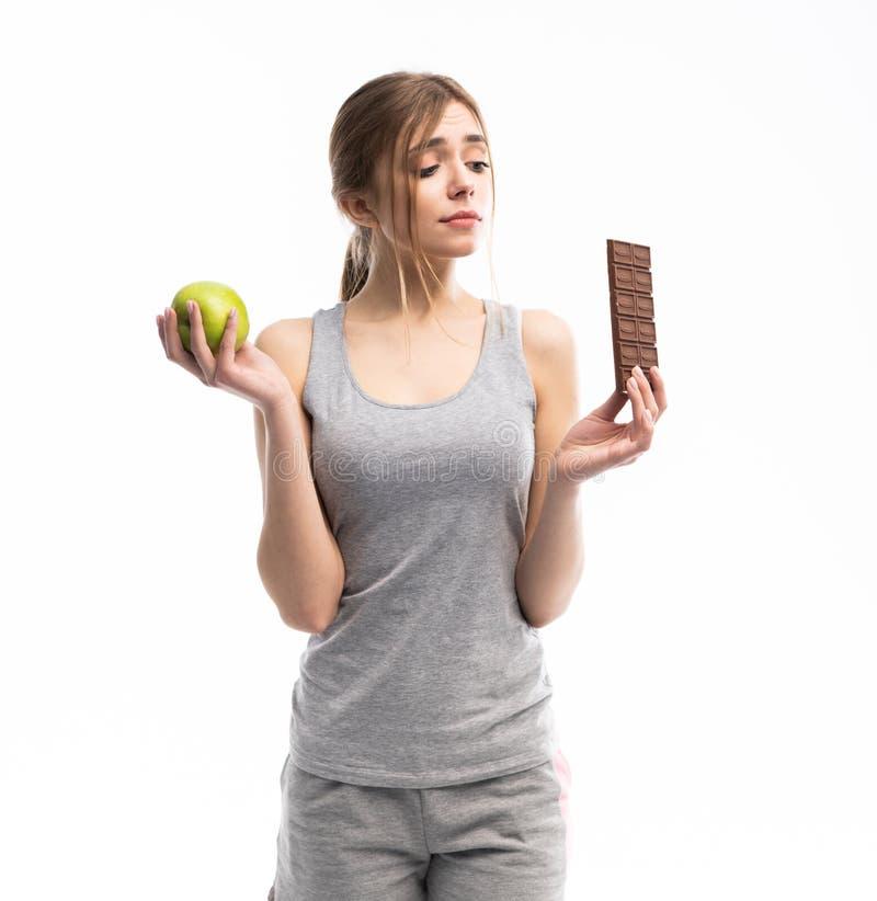 Dieet Het op dieet zijn concept Gezond voedsel Mooie Jonge Vrouw die tussen Gezond en Ongezond Voedsel kiezen Vruchten of snoepje royalty-vrije stock afbeelding