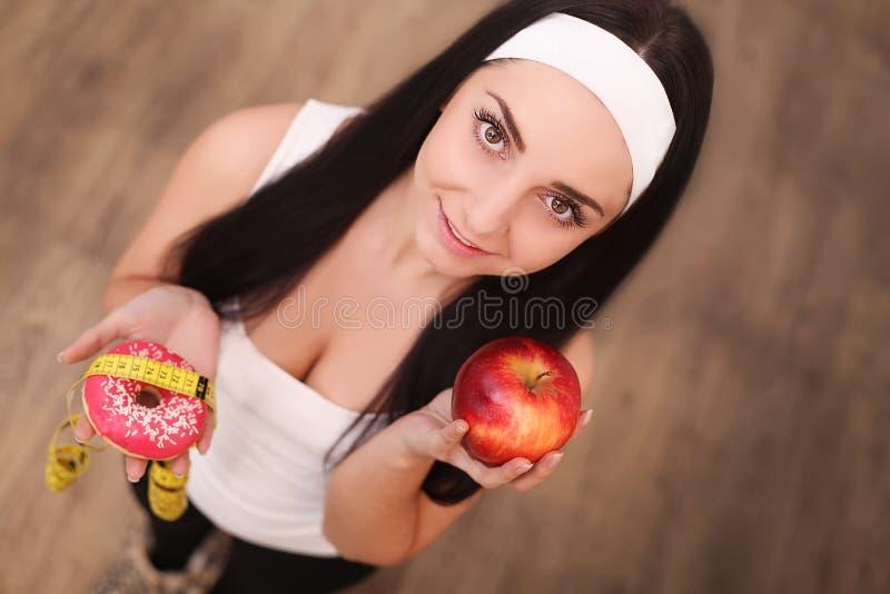 Dieet Het op dieet zijn concept Gezond voedsel Mooie Jonge Vrouw die tussen Vruchten en Snoepjes kiest stock fotografie