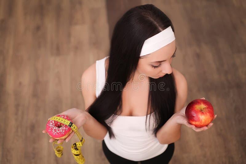 Dieet Het op dieet zijn concept Gezond voedsel Mooie Jonge Vrouw die tussen Vruchten en Snoepjes kiest stock afbeelding