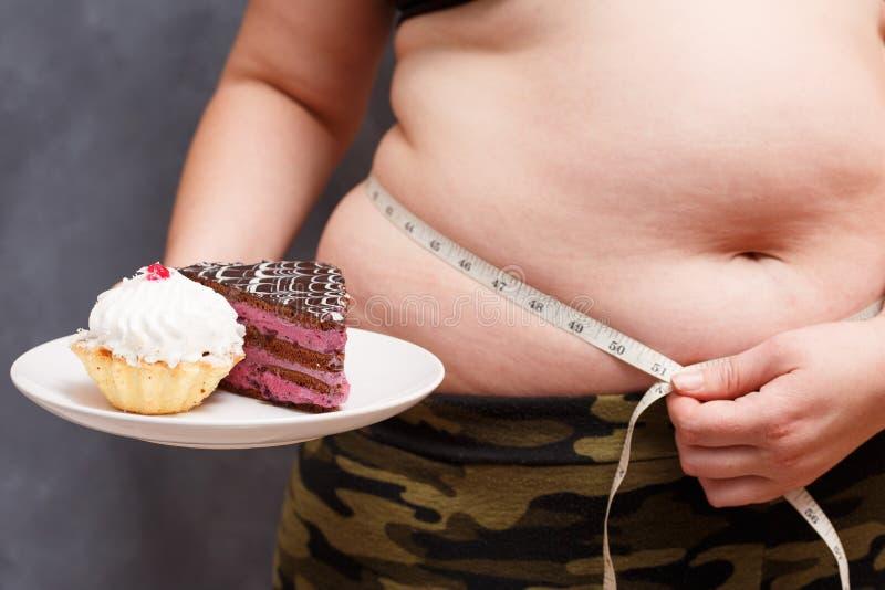 Dieet, het op dieet zijn, ongezonde kostconcept Sluit omhoog van jonge zwaarlijvige overwe royalty-vrije stock foto's