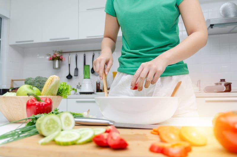 Dieet. jonge mooie vrouw in een groen hemd die staat en de groentesalade klaarmaakt voor een goede gezondheid in de moderne keuken stock fotografie