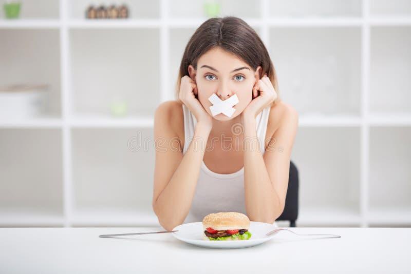 Dieet Jonge vrouw met buisband over haar mond, die haar verhinderen stock foto