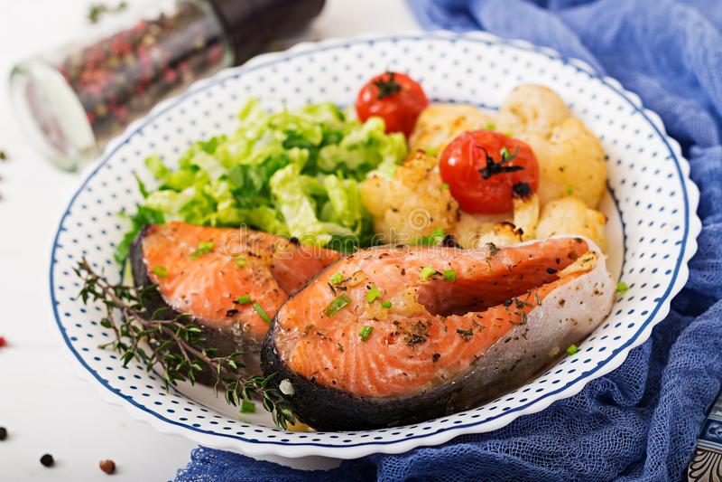 Dieet menu Gebakken zalmlapje vlees met bloemkool, tomaten en kruiden royalty-vrije stock foto's