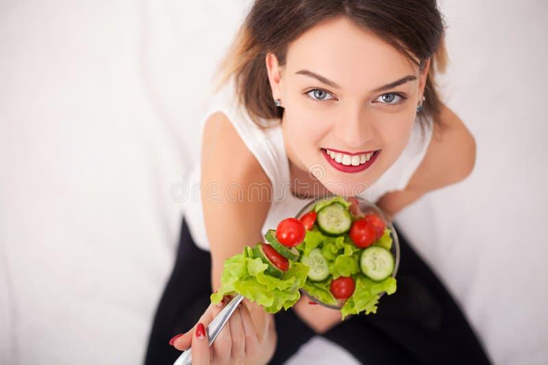 Dieet Mooie jonge vrouw die plantaardige salade eet stock foto