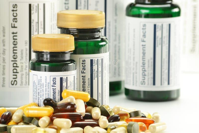 Dieet supplementcapsules en containers stock afbeeldingen